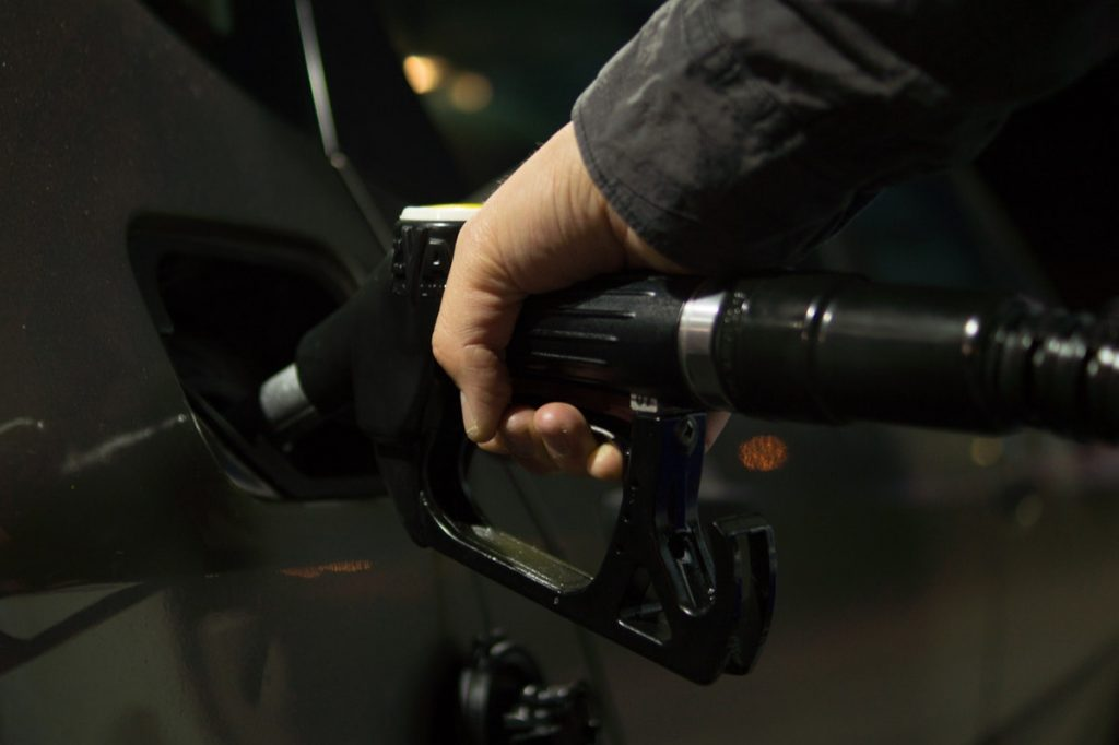 Does the Brand of Gas I Use in my Car Actually Matter? Hand pumping gasoline into car